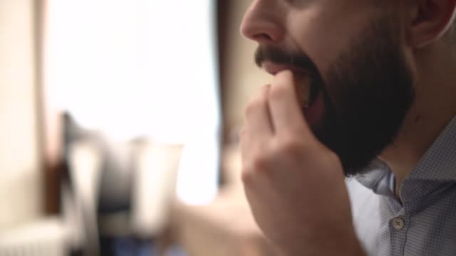 Young man eating breakfast at the restaurant Close-up footage of young man's mouth chewing piece of bread with butter fork stock videos & royalty-free footage