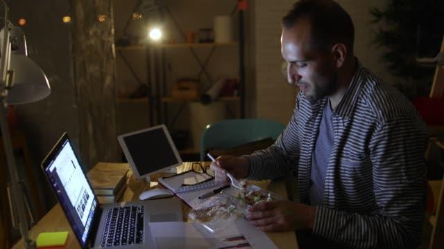オフィスで若い男を食べるファーストフード - 不健康な食事点の映像素材/bロール