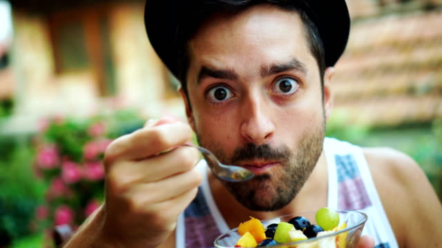 Young man eating fruit salad video