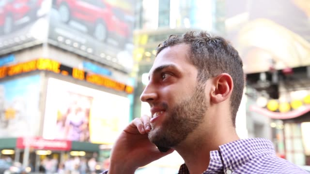 Young man enjoying a great time while talking on the phone in Times Square, Manhattan, New York City, USA