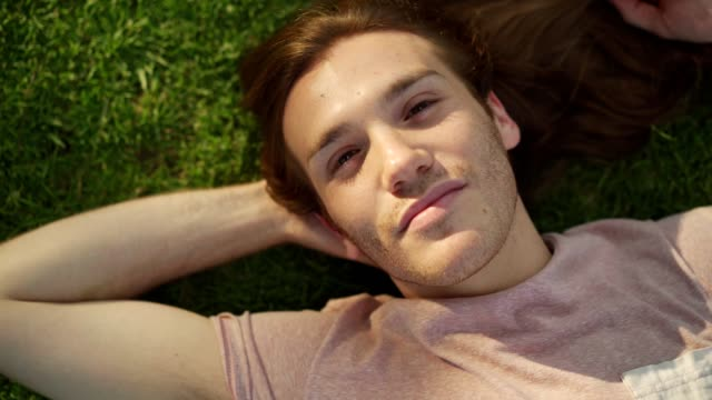 Young man enjoying sunny day Young man is lying down on a lawn, looking at camera and smiling. long hair stock videos & royalty-free footage
