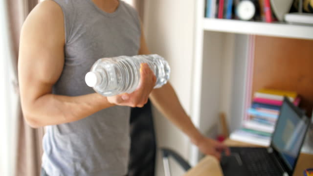 young man exercise at home without traditional equipment during coronavirus covid-19 quarantine - ludzka kończyna filmów i materiałów b-roll