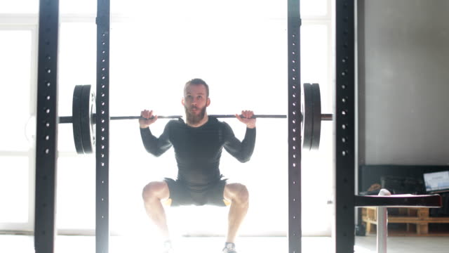 Young Man Exercising Doing Weighted Squats On Smith Machine During Workout Training At Gym video