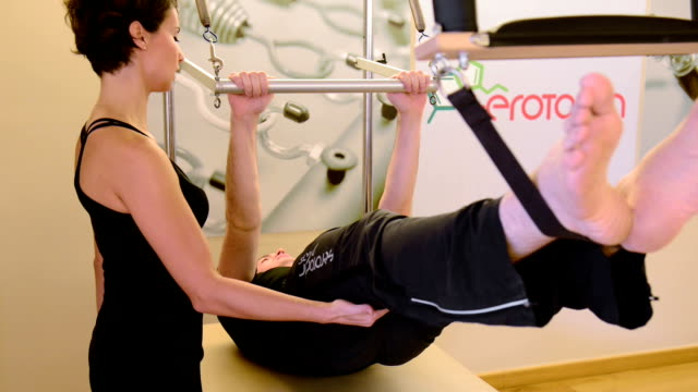 Young man exercising in the pilates studio video