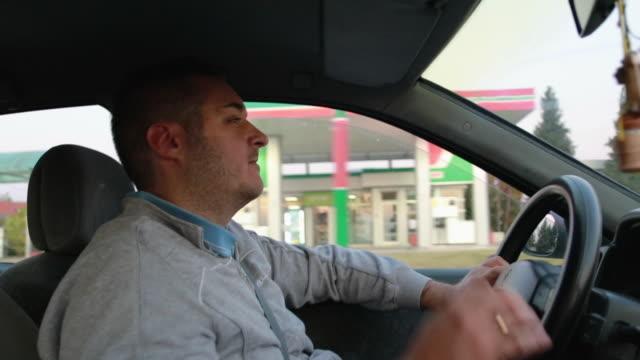 車の中で疲れを感じている若者。車を運転しながら、疲れ果てた男があくびをして手で口を覆う - リスク点の映像素材/bロール