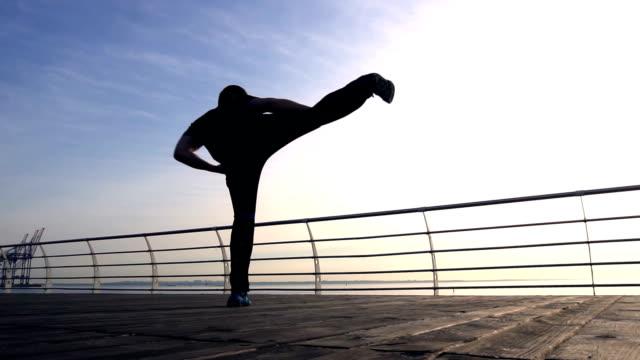 Junger Mann kämpfen Training gegen Sonnenaufgang in Zeitlupe – Video