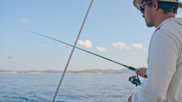 4K Young man fishing on boat on sunny ocean, real time 4K Young man fishing on boat on sunny ocean. MS, real time. fishing rod stock videos & royalty-free footage