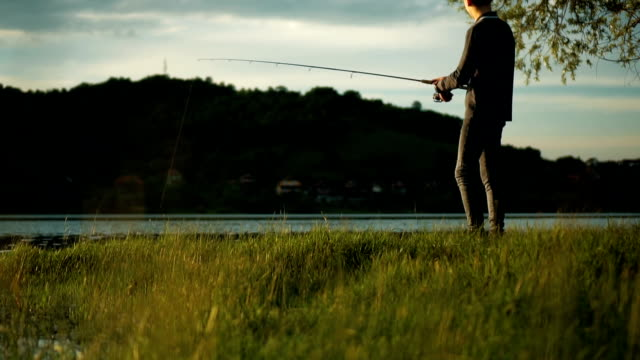Young man fishing Young, fisherman is fishing on the lake in beautiful sunny day. fishing rod stock videos & royalty-free footage