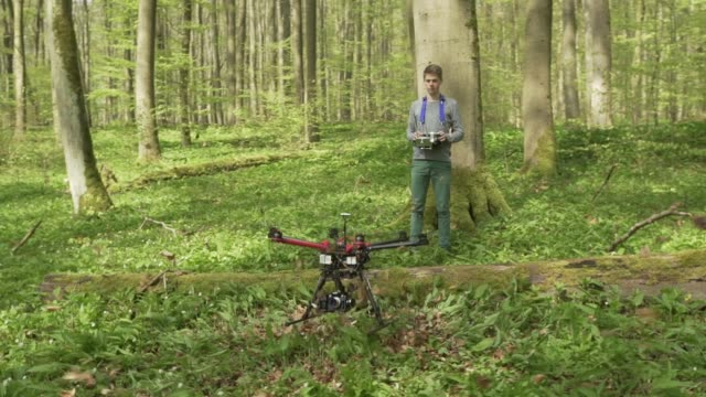 Young man flies drone in forest video