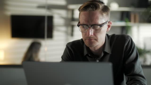 genç adam freelancer kullanarak laptop online office ofis ten çalışma internet, gülümseyen odaklı milenyum guy bilgisayar sörfü web tarama ekran uzak i̇ş zevk - çekici insanlar stok videoları ve detay görüntü çekimi