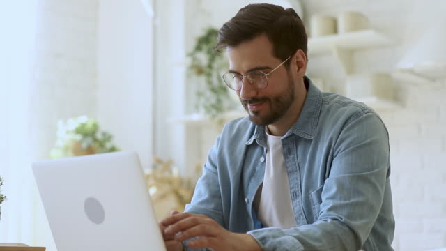 young man freelancer using laptop studying working online at home - didattica a distanza video stock e b–roll