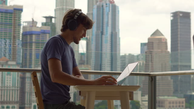 Young man freelancer workes on his laptop at a balcony with a background of a city center full of skyscrapers. Remote techer has a conversation with a student through the internet