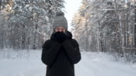 istock young man froze in snow forest. warms his hands in black mittens. 1204229503