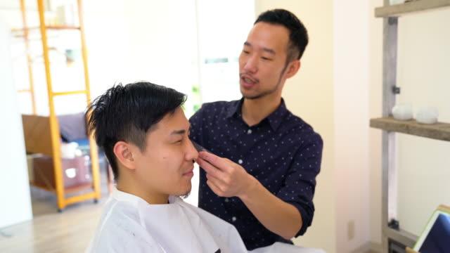若い男を得る彼の髪をカットやスタイルのヘアサロンで - 美容院点の映像素材/bロール