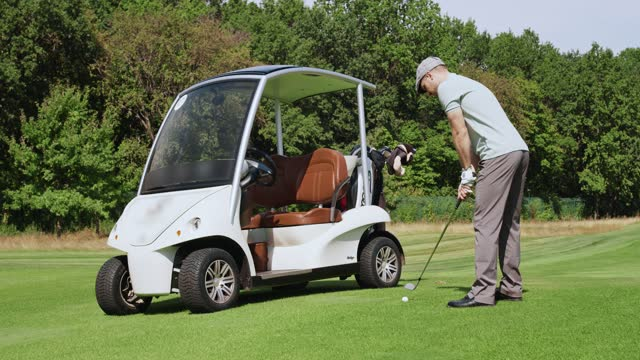 Young man getting away from electric golf car, taking golf stick from back and swinging it