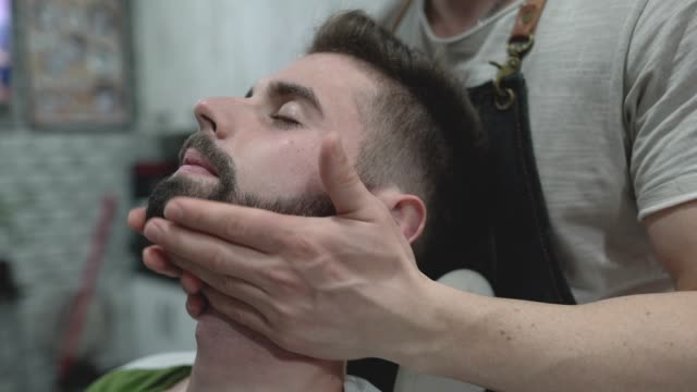 young man getting facial massage after beard grooming - baffo peluria del viso video stock e b–roll
