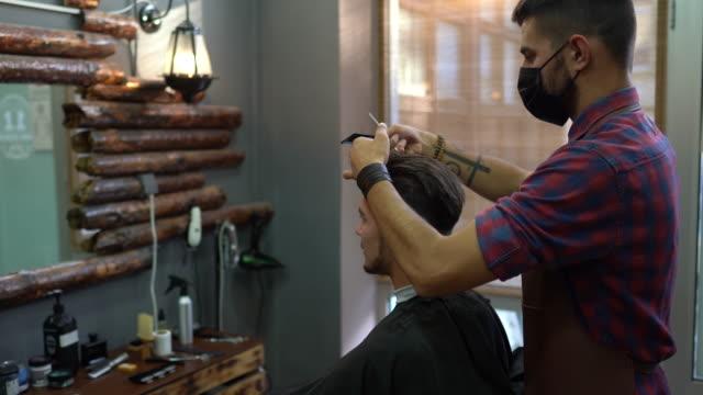 stockvideo's en b-roll-footage met jonge mens die kapsel bij de kapperswinkel krijgt - mirror mask