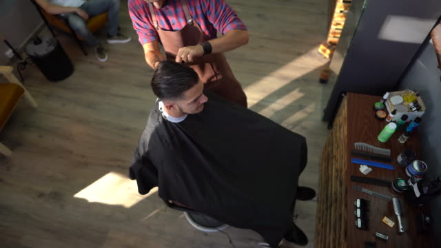 Young man getting his haircut by barber at barber shop