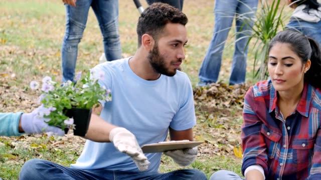 junger mann gibt anweisungen zum freiwilligen während community outreach event - gärtnerisch gestaltet stock-videos und b-roll-filmmaterial