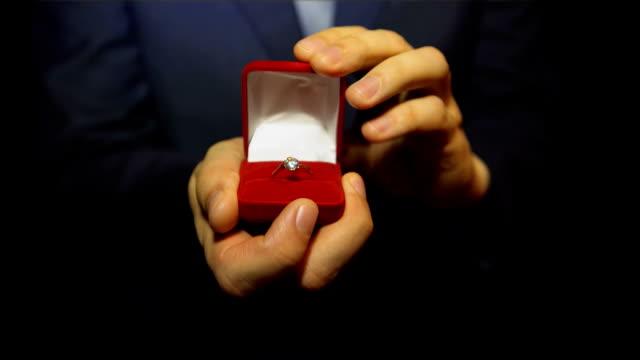 vídeos y material grabado en eventos de stock de joven hombre dando un anillo con diamante en la caja - prometido