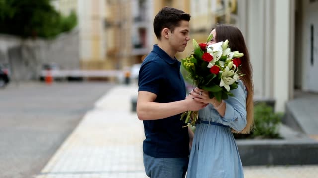 Young man giving bunch of flowers to girl on date video