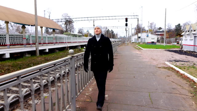 Young man go along empty railway, stop to look back and pass by video