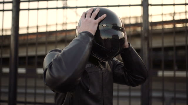 A young man goes to his motorcycle, sits on it and puts a helmet to go on a journey A young man goes to his motorcycle, sits on it and puts a helmet to go crash helmet stock videos & royalty-free footage