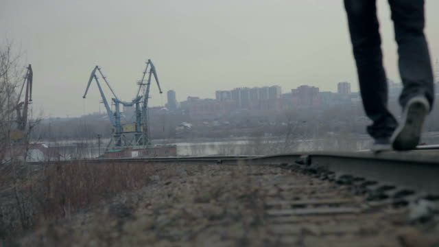 Young man goes to rail against backdrop of the city video