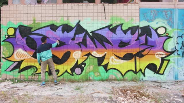 Young man graffiti artist painting on the wall, exterior Young man graffiti artist painting on the wall, exterior mural stock videos & royalty-free footage
