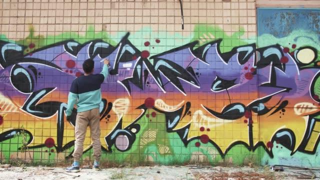 ung man graffitikonstnär måla på väggen, exteriör - väggmålning bildbanksvideor och videomaterial från bakom kulisserna