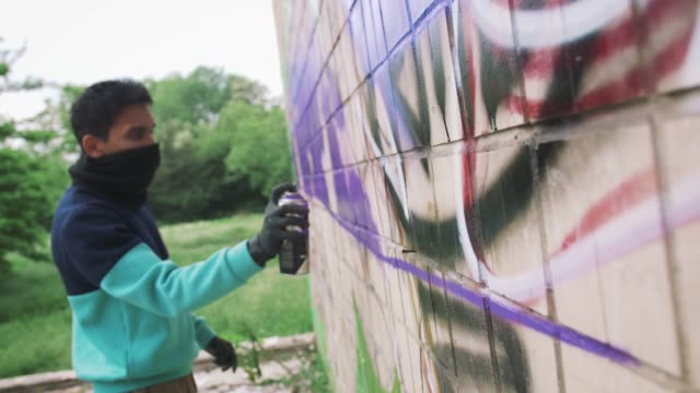 Young man graffiti artist painting on the wall, slow motion, dolly shot