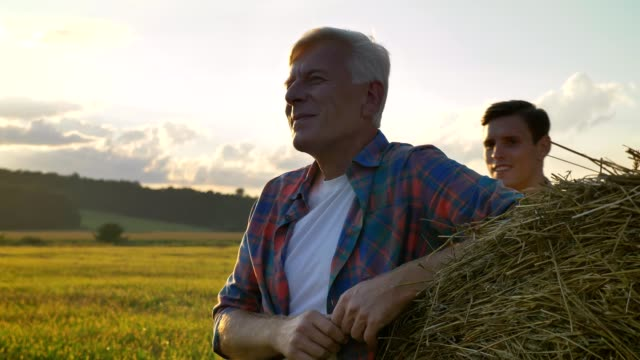 Young man greeting old farmer and shaking his hand, going away on straw field, beautiful landscape during sunset in background