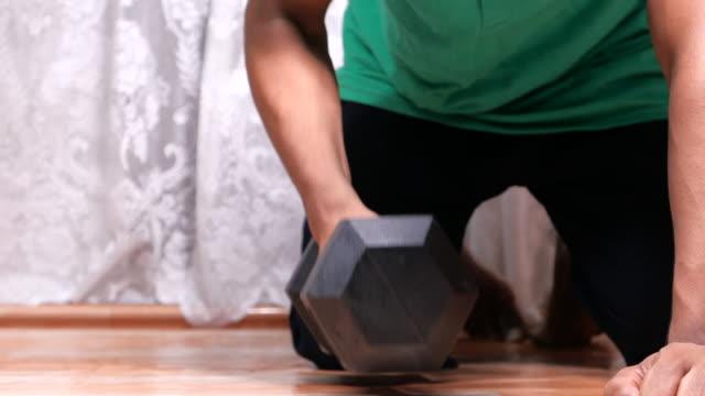 vidéos et rushes de jeune homme exercice de la main avec haltères à l'intérieur. - bras humain
