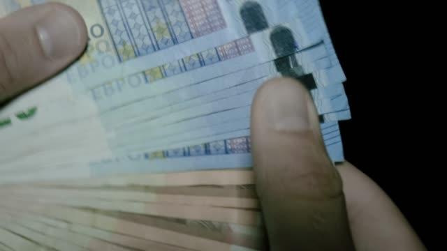 молодой человек руки раздувание евро банкноты - white background стоковые видео и кадры b-roll