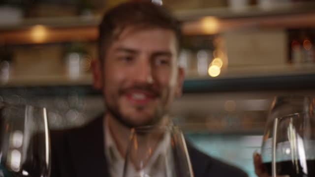 若い男がある友人スローモーション 4 k で乾杯 - 赤ワイン点の映像素材/bロール