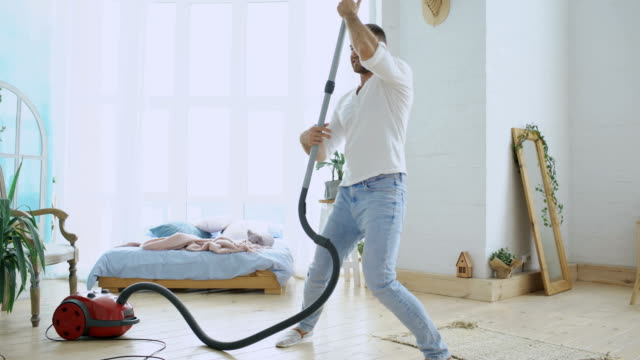 Junger Mann Spaß Hausputz mit Staubsauger tanzen wie mit Frau – Video
