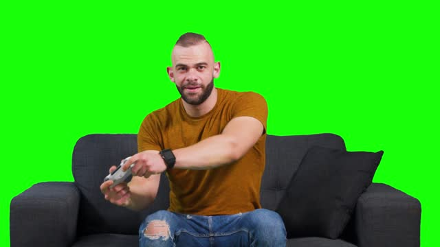 Young man having fun playing video games sitting on sofa Young hipster man having fun using gaming controller and playing video games against green background physical position stock videos & royalty-free footage
