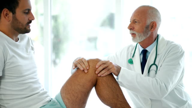 Young man having his knee examined 4k video