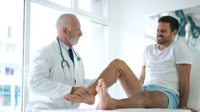 young man having his knee examined. - fisioterapia video stock e b–roll