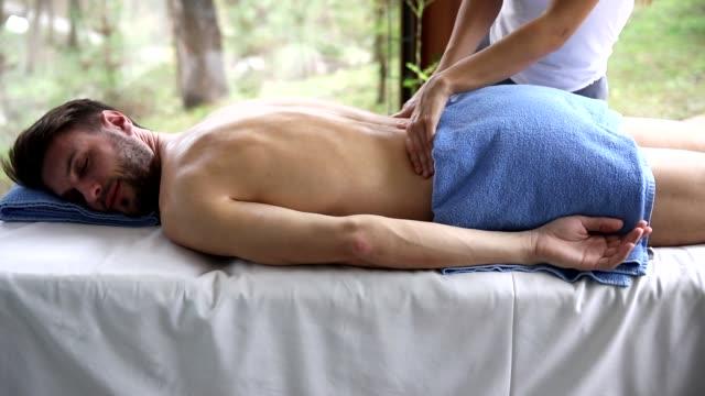 genç adam sakin ol spa'da masaj sahip - i̇nsan sırtı stok videoları ve detay görüntü çekimi