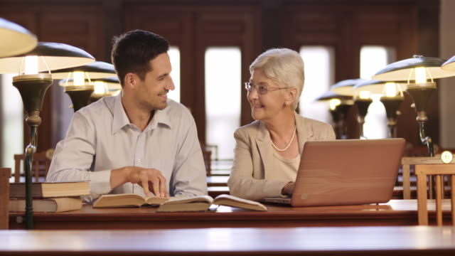 DS Young man helping a senior woman learn how to use a laptop in a library video