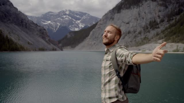 Young man hiker arms outstretched at mountain lake video