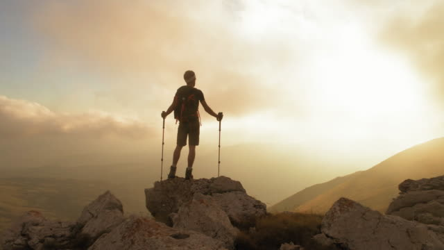 young man hiker standing on ridge edge of the mountain in abruzzo italy with poles at sunset - klif filmów i materiałów b-roll