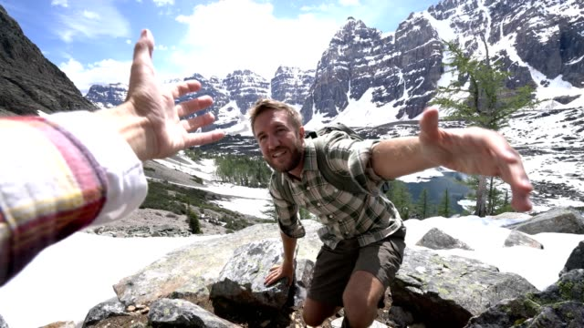 young man hiking in the canadian rockies, hand reach out to help - fiducia video stock e b–roll