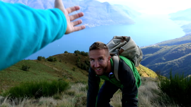 Young man hiking pulls out hand to get assistance video
