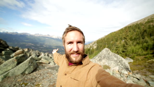 Young man hiking takes selfie portrait in mountain top video