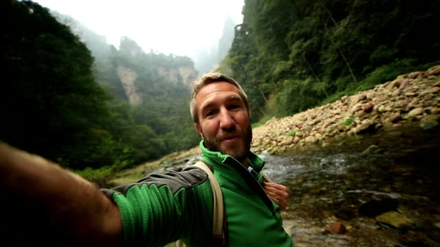Young man hiking takes smart phone selfie, China video