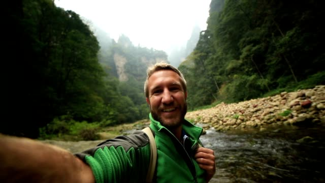 young man hiking takes smart phone selfie, china - trekking video stock e b–roll