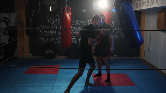 young man hitting punching bag on kick box training with his coach - sparring allenamento video stock e b–roll