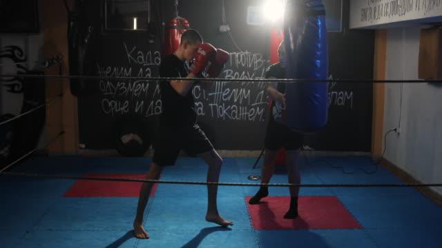 vídeos de stock, filmes e b-roll de jovem acertando saco de pancadas em treinamento de kick box com seu treinador - 16 17 anos